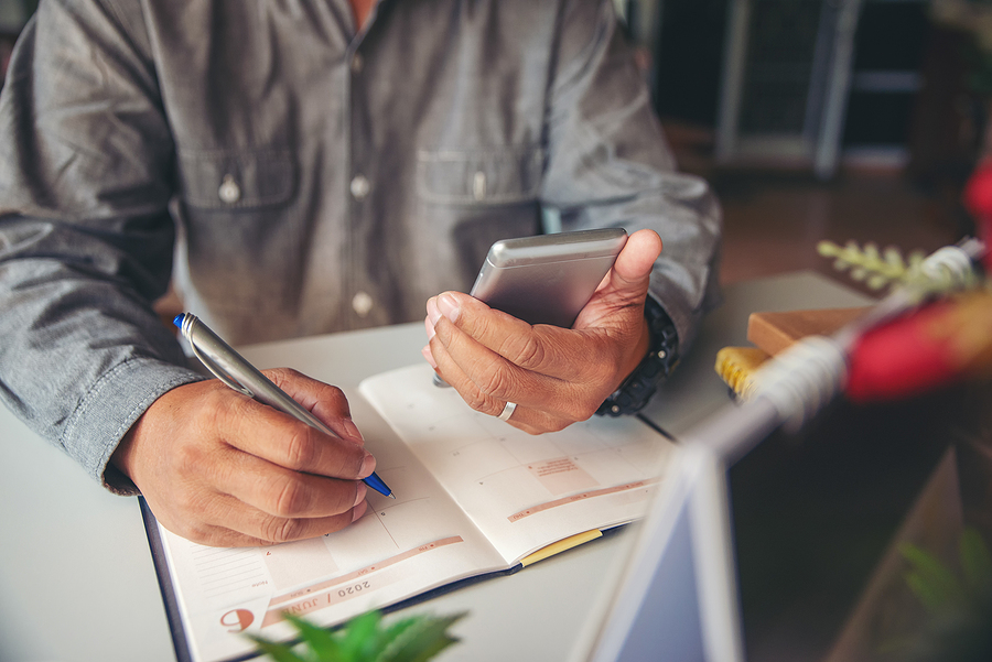 Man Checking Phone and Calendar for scheduling